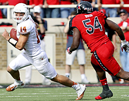 Texas' David Ash runs from Texas Tech's Dartwan Bush while passing for three touchdowns and 264 yards. (AP)