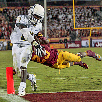 Oregon's Kenjon Barner gets by Southern California's Nickell Robey to score one of his five touchdowns. (AP)