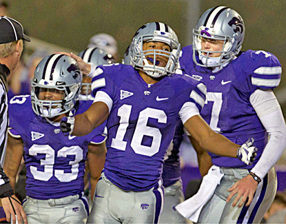 Tyler Lockett (center) and Collin Klein (right) celebrate a touchdown by running back John Hubert (left) in the Wildcats' win. (AP)