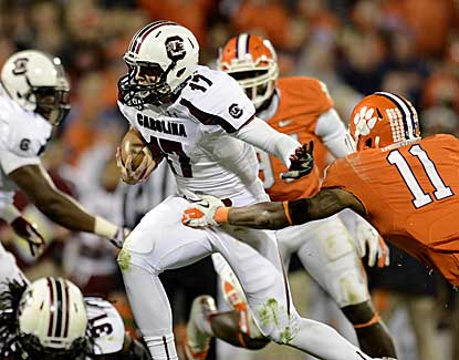 South Carolina quarterback Dylan Thompson escapes the grasp of Clemson's Travis Blanks. (AP)