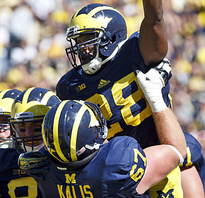 Fitzgerald Toussaint gets a lift after his late touchdown helps Michigan avoid a humiliating home defeat.  (USATSI)