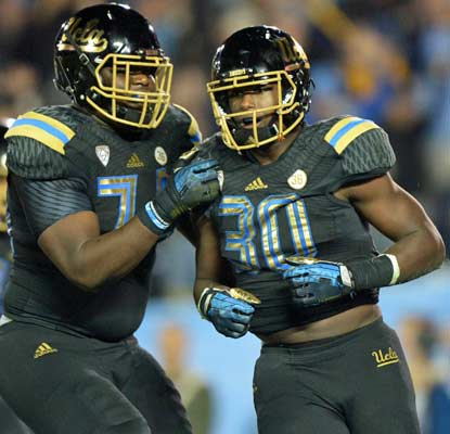 Myles Jack (30), a linebacker, plays running back and piles up four touchdowns for the 13th-ranked Bruins.  (USATSI)