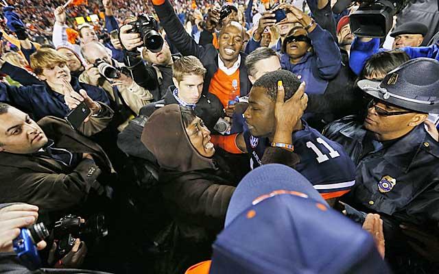 Chris Davis hugs his mother amid a swarm of fans after his winning kick return.  (USATSI)