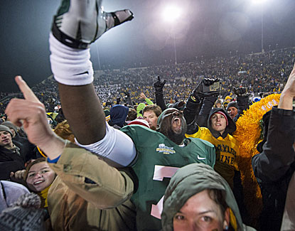 Baylor players celebrate on the field with fans after winning the school's first outright conference title since 1980. (USATSI)
