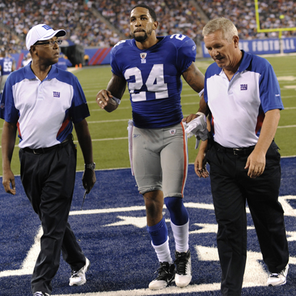 Giants starting cornerback Terrell Thomas hobbles off the field after tearing his ACL in the first half. (Getty Images)