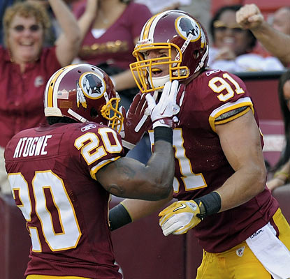 Oshiomogho Atogwe celebrates with Ryan Kerrigan (91), who picks off an errant Eli Manning pass and turns it into six points. (AP)