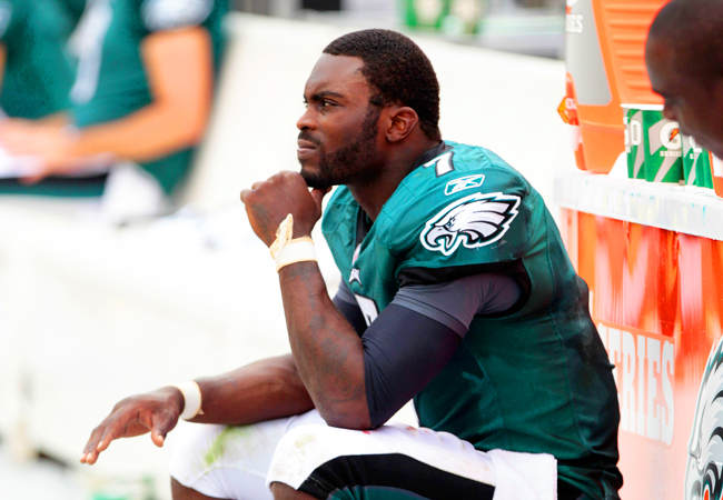 Michael Vick watches his team battle the Giants after suffering a bruised right hand. (Getty Images)