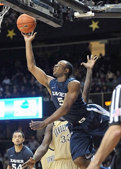 Xavier's Dezmine Wells attempts an acrobatic shot around Vanderbilt forward Steve Tchiengang (33) during overtime.  (US Presswire)