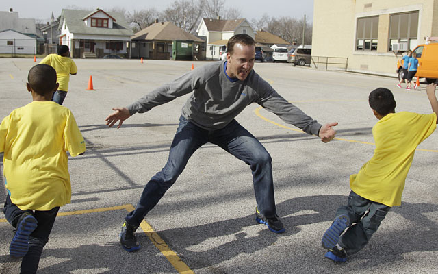 Peyton Manning at play with some Indy kids, who should be familiar with his recent childish behavior. (AP)