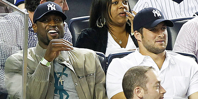 Tim Tebow, sitting with the Heat's Dwyane Wade, gets an inhospitable greeting in the Bronx. (US Presswire)