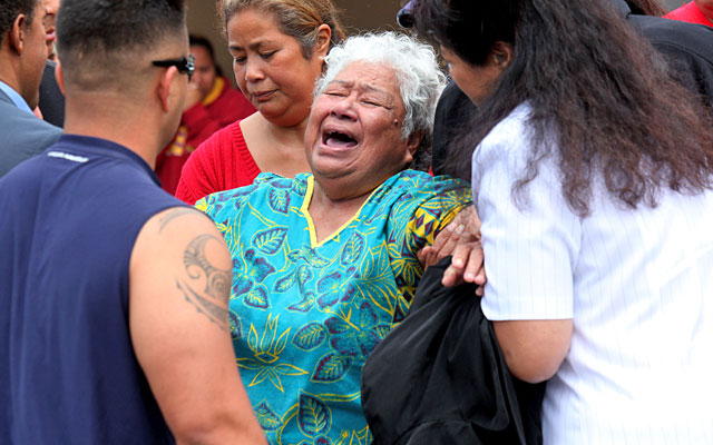 Luisa Seau is consoled by family and friends Wednesday after learning of her son's suicide. (Getty Images)