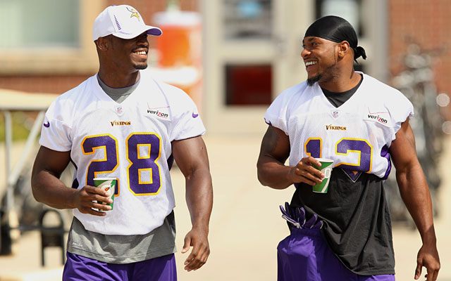 Adrian Peterson walks to practice with Percy Harvin, but doesn't get to participate. (AP)