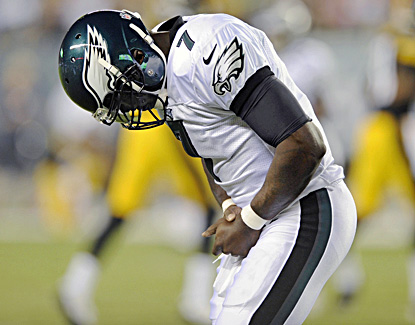 Michael Vick holds his thumb after hitting a helmet during a pass attempt. X-rays were negative. (AP)