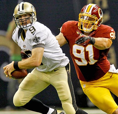 Drew Brees (339 yards, three TDs, two INTs) tries to get away from fellow Purdue Boilermaker Ryan Kerrigan.  (US Presswire)