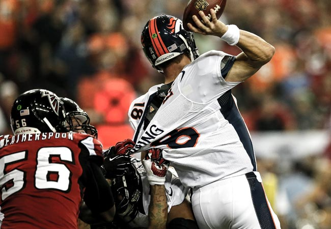 Peyton Manning is taken down by the Falcons' John Abraham and Kroy Biermann. (Getty Images)