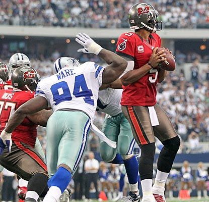 Josh Freeman doesn't know it, but Dallas' DeMarcus Ware is about to strip the ball away from behind.  (US Presswire)