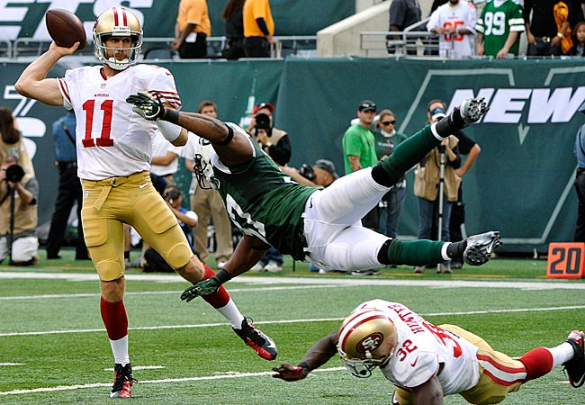49ers QB Alex Smith throws a pass away from Jets S Yeremiah Bell. (AP)