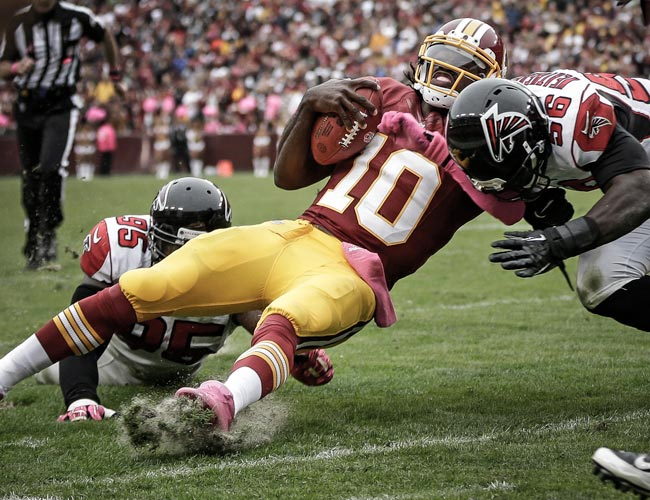 Robert Griffin III is hit by Falcons Sean Weatherspoon and Jonathan Babineaux. (AP)