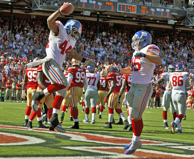 Ahmad Bradshaw (left), who rushes for 116 yards against the 49ers, scores a touchdown. (Getty Images)