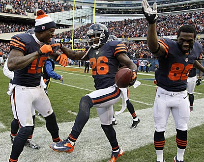 Teammates Brandon Marshall (15) and Earl Bennett (80) help cornerback Tim Jennings (26) celebrate his pick-six.  (AP)
