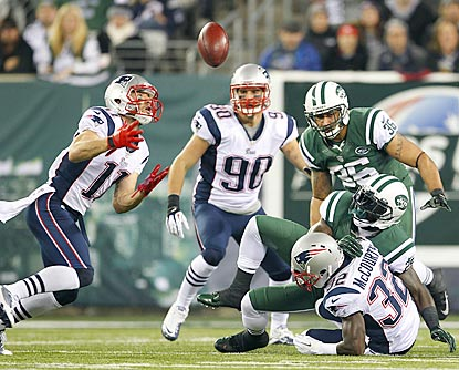 A fumble by Joe McKnight (bottom) lands in the hands of Julian Edelman, who returns it for a touchdown.  (Getty Images)
