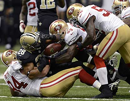San Francisco's Justin Smith (94) and NaVorro Bowman (53) jar the ball loose from Mark Ingram. (AP)