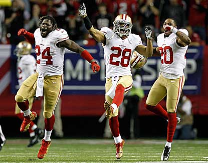 Anthony Dixon (left), Darcel McBath (center) and Perrish Cox celebrate a late defensive stop. (Getty Images)