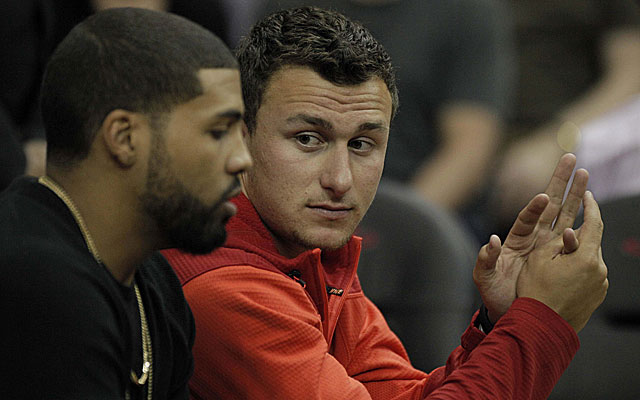 Johnny Manziel with Texans RB Arian Foster at a recent Rockets game. (USATSI)