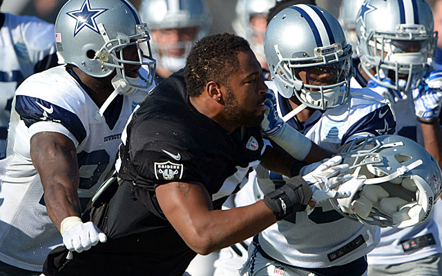 Cowboys players restrain Raiders linebacker Justin Cole during a scrimmage.  (USATSI)