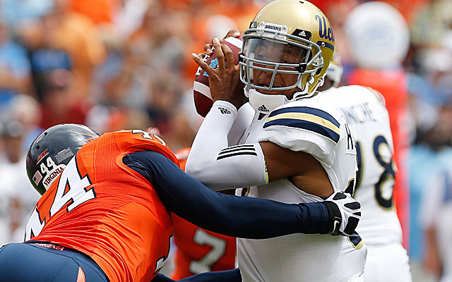 UCLA's Brett Hundley is wrapped up by a Virginia defender.  (USATSI)