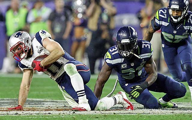 Julian Edelman staggers to his feet after a vicious hit by Kam Chancellor.  (Getty Images)