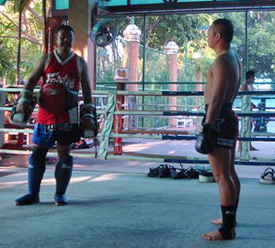 Yod (right) and his trainer take a break during training at the Fairtex complex. (Mike Freeman)