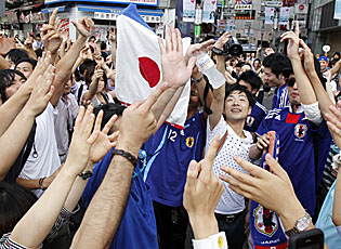 Fans in Tokyo lift the Japanese flag in celebration after Japan wins its first Women's World Cup. (AP)