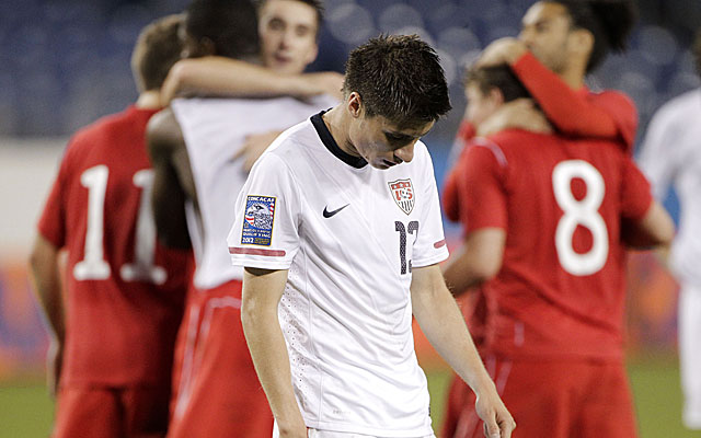Jorge Villafana of the U.S. leaves the field as the Canadians celebrate in the background. (AP)