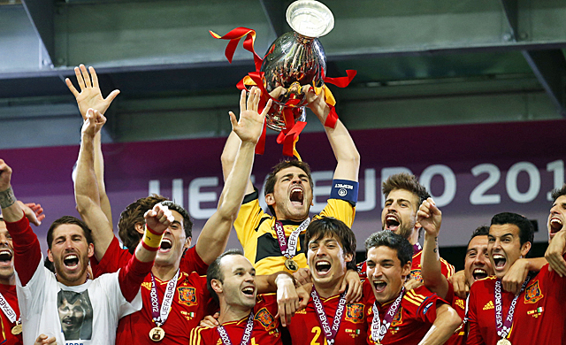Iker Casillas holds up the trophy as Spain celebrates its third straight major tournament victory. (AP)
