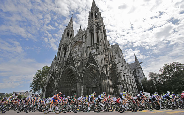 The Tour de France pack rides by a church in Rouen at the start of the fifth stage. (AP)