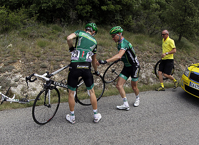 Riders help with a tire change after hitting a stretch of tacks on the road. (Getty Images)