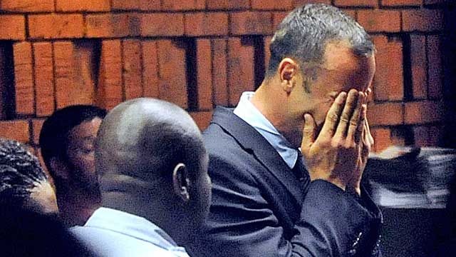 Pistorius hides his face in his hands in the court room during his hearing Friday. (Getty Images)