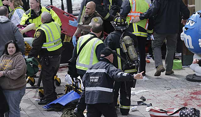 Police and fire rescue personnel move onto the scene after the explosions. (AP)