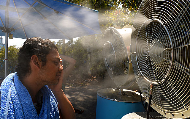 A tennis fan tries to cool off from the extreme heat at the Australian Open. (Getty)