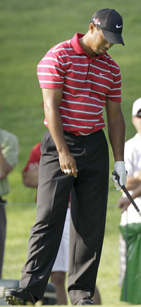 Tiger Woods can't make sense of another wayward tee ball. (AP)