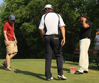 Padraig Harrington (middle) sorts out his tee-box confusion with Phil Mickelson and rules offical Ronan Flood. (Getty Images)