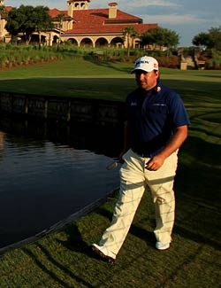 Graeme McDowell walks to the first tee as the sun begins to set at TPC Sawgrass. (Getty Images)