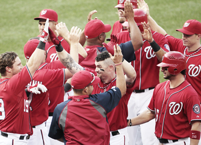 With the bases loaded in the bottom of the 10th, Brad Lidge nicks Jonny Gomes (center) with a pitch giving Washington the win. (AP)