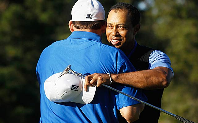 Tiger Woods gets a hug from partner Tony Romo, who thinks Woods has a 'great shot this week.' (Getty Images)