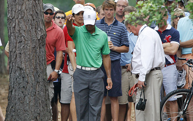 With the ball from his approach at No. 5 nowhere(?) to be found, Tiger Woods gets a drop. (AP)