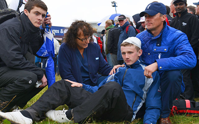 A young fan needs a bandage after taking a Rory McIlroy drive to the head at the 15th hole. (Getty Images)