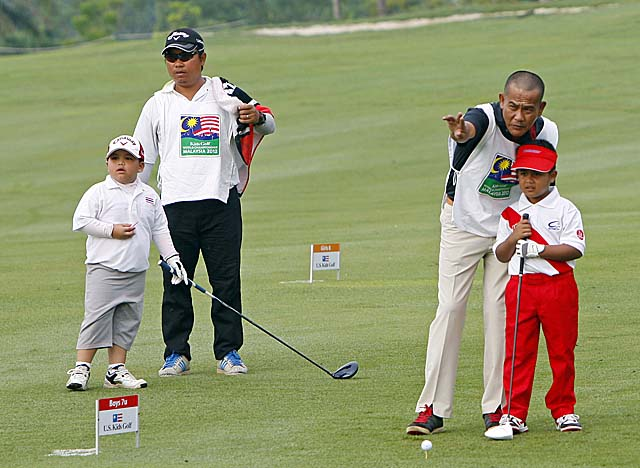 Two competitors get help from their dads at the Kids Golf World Championship in  Malaysia. (AP)