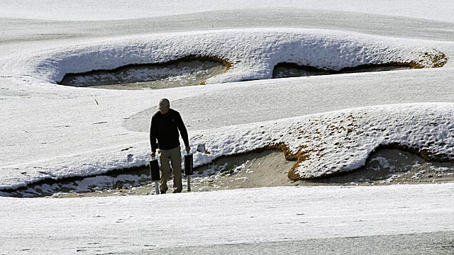 A worker picks up practice balls out of bunkers on the practice range before play resumes. (AP)