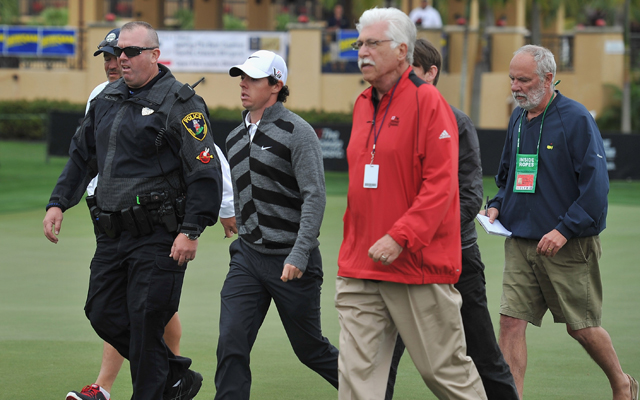 Rory McIlroy begin escorted off the course. (Getty Images)